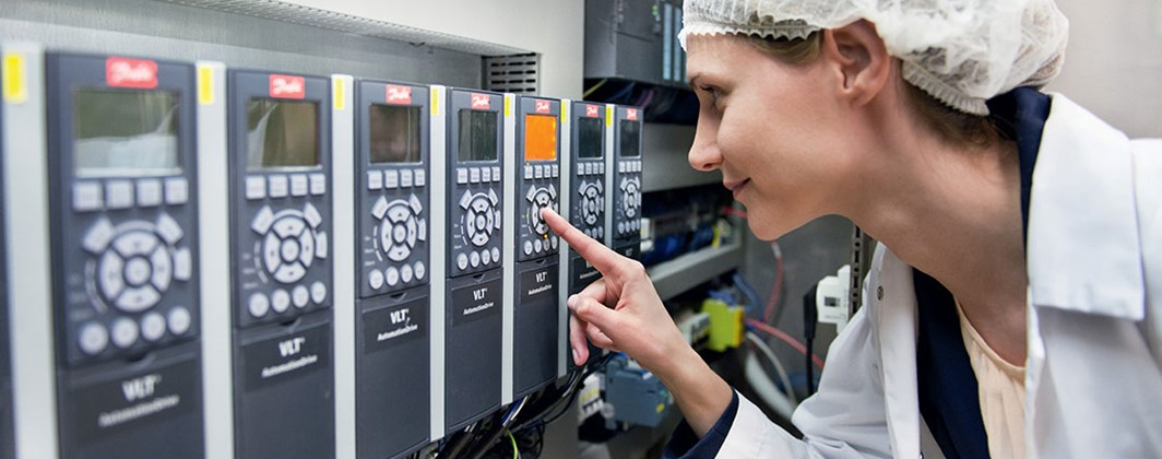 Photo of a Danfoss employee checking the settings on a single VLT drive in a row of them