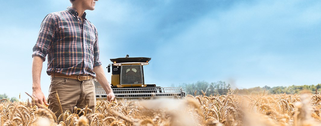 Photo of a farmer in a field of wheat with a plow in the background on a clear, sunny day.