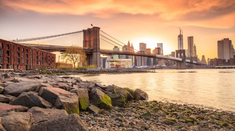 Photo of the Brooklyn Bridge in New York at sunset with the New York City skyline in the background.